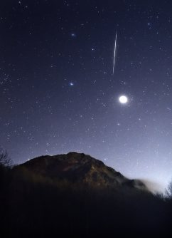 誕生から今年で70年を迎えた昭和新山の上空に流れる、ふたご座流星群の流れ星。右の星は木星=北海道壮瞥町で2015年12月14日午前2時40分、手塚耕一郎撮影