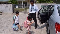 迎えに来た父親と一緒に保育園を出る子供たち=埼玉県鶴ヶ島市のかこのこ保育園で2015年8月4日、関口純撮影