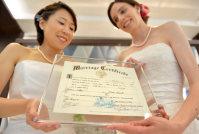 米オレゴン州で発行された結婚証明書を手にする坂田さん(左)とスティーガーさん=京都市下京区で2015年10月、大西岳彦撮影