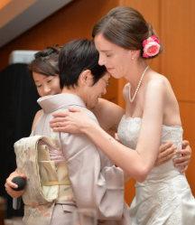 坂田さんの母里英子さん(65)=中央=と抱き合うスティーガーさん(右)と坂田さん=京都市下京区で2015年10月、大西岳彦撮影