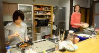 自宅でランチのパスタを作る坂田さん(左)とスティーガーさん=京都市下京区で2015年11月、大西岳彦撮影