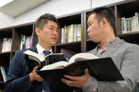 事務所で話し合う南さん(左)と吉田さん=大阪市北区で2015年12月、大西岳彦撮影