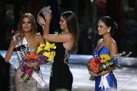 Former Miss Universe Paulina Vega, center, removes the crown from Miss Colombia Ariadna Gutierrez, left, before giving it to Miss Philippines Pia Alonzo Wurtzbach, right, at the Miss Universe pageant on Dec. 20, 2015, in Las Vegas. (AP Photo/John Locher)
