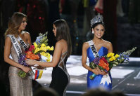 Former Miss Universe Paulina Vega, center, takes away the flowers and sash from Miss Colombia Ariadna Gutierrez, left, before giving it to Miss Philippines Pia Alonzo Wurtzbach, right, at the Miss Universe pageant on Dec. 20, 2015, in Las Vegas. (AP Photo/John Locher)