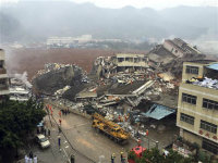 Rescuers search for survivors amongst collapsed buildings after a landslide in Shenzhen, Guangdong province in southern China on Sunday, Dec. 20, 2015. The landslide collapsed and buried buildings at and around an industrial park in the city on Sunday, authorities reported. (Chinatopix via AP)