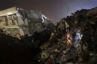 Rescuers search for survivors amongst collapsed buildings in the aftermath of a landslide in Shenzhen in south China's Guangdong province on Sunday Dec. 20, 2015. (Color China Photo via AP)