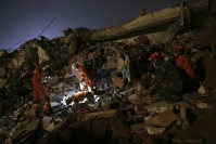Rescuers search for survivors amongst collapsed buildings in the aftermath of a landslide in Shenzhen in south China's Guangdong province on Dec. 20, 2015. (Color China Photo via AP)