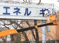 帰還困難区域にある原発PR看板の撤去作業が始まり、文字パネルを取り外す作業員=2015年12月21日、佐々木順一撮影