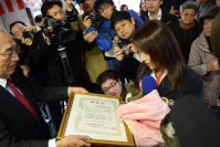 Bus the honorary stationmaster cat at Aizu Railway's Ashinomaki Onsen Station receives a certificate of merit for her years of service, on Dec. 24, 2015. (Mainichi)