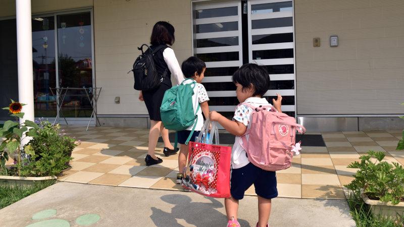 お母さんに連れられて保育園に到着した子供たち=埼玉県鶴ヶ島市のかこのこ保育園で、関口純撮影