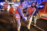 11月13日、同時多発テロの被害にあったパリのバタクラン劇場から担架で女性を運ぶ救助隊員=AP