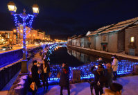 Visitors snap photos of lights decorating the Otaru Canal in the city of Otaru, Hokkaido. (Mainichi)