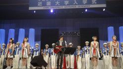 近畿大の入学式を演出し、自らギターで校歌も演奏するつんく♂さん(中央)=東大阪市で2015年4月4日午前11時32分、三村政司撮影