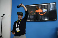 Matthew Taylor paints in 3D virtual reality at the Intel booth using HTC Vive virtual reality goggles at CES International, on Jan. 6, 2016, in Las Vegas. (AP Photo/John Locher