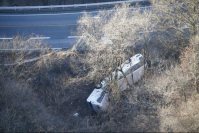 A tour bus lies on its side next to National Route 18 in Karuizawa, Nagano Prefecture, after crashing through the guardrail, on Jan. 15, 2016. (Mainichi)