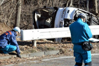 A tour bus that had been carrying people to a ski resort lies on its side by National Route 18 after crashing through a guardrail early on the morning of Jan. 15, 2016. A police investigator can be seen next to the bus. (Mainichi)