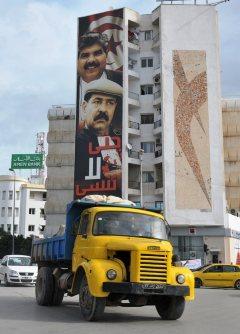 国家議事堂の前に掲げられた2013年に相次いで殺害された世俗派の野党指導者の顔写真の横断幕。「我々は忘れてはならない」と書かれている=チュニスで4日、賀有勇撮影