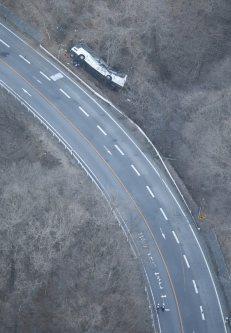 ガードレールを突き破り、道路脇に転落したバス=長野県軽井沢町で2016年1月15日午前7時44分、本社ヘリから