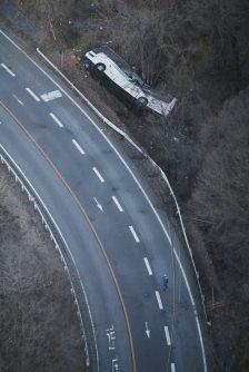 ガードレールを突き破り、道路脇に転落したバス=長野県軽井沢町で2016年1月15日午前7時27分、本社ヘリから