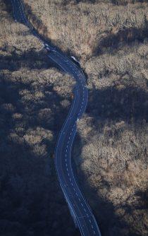 ガードレールを突き破り、道路脇に転落したバス=長野県軽井沢町で2016年1月15日午前8時1分、本社ヘリから