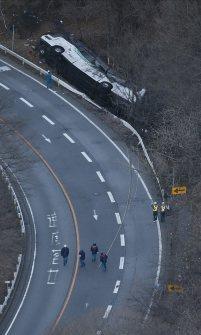 ガードレールを突き破り、道路脇に転落したバス=長野県軽井沢町で2016年1月15日午前7時半、本社ヘリから