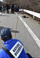 ガードレールを突き破り転落した観光バスのタイヤ痕を調べる国交省の事業用自動車事故調査委員会の関係者=長野県軽井沢町で2016年1月15日午後2時50分、宮間俊樹撮影