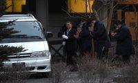 遺体安置所から出る犠牲者の棺と遺族が乗った車を見送る警察官ら=長野県軽井沢町で2016年1月15日午後4時51分、丸山博撮影