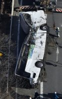 クレーン車で路上に移動されたスキーバス。天井がひしゃげて車体がくの字に折れ曲がっている=長野県軽井沢町で2016年1月15日午後1時17分、本社ヘリから