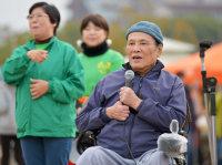 東北と関西の障害者交流イベントであいさつをする牧口一二さん。被災障害者に救援金を送り続けている=大阪市東住吉区で、三浦博之撮影