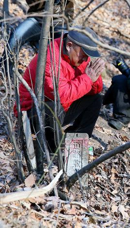 スキーバスが転落した現場に手を合わせる男性=長野県軽井沢町で2016年1月16日午前8時4分、森田剛史撮影