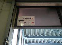 出口の上部に「府中刑務所」と「農工大」への矢印=銅崎順子撮影