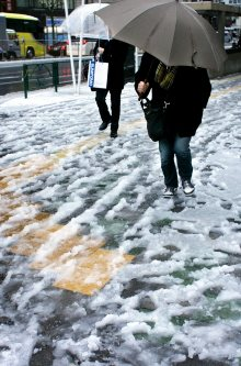 足元に気をつけながら雪が残る道を歩く人たち=東京都中央区で2016年1月18日午前8時38分、森田剛史撮影