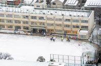 雪に覆われた校庭を通って元気に登校する児童たち=東京都世田谷区で2016年1月18日午前8時14分、本社ヘリから喜屋武真之介撮影