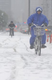 積雪で足場が悪い中自転車に乗る男性=東京都千代田区で2016年1月18日午前9時54分、猪飼健史撮影