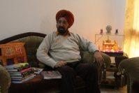 自宅の応接間で取材に応じるバリンダル・シン・ワーリヤ教授。傍らには黄金寺院のミニチュアが飾られていた=インド北西部パティヤラで2015年11月28日午後0時54分、金子淳撮影