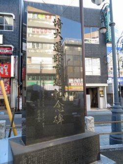 バス停の少し先に「埼大道路貫通記念碑」。北浦和駅からの直線道路を通すため、関係者が東奔西走し、昭和50年2月、14億200万円で完成、とある。期成同盟の最高顧問は松永東・元衆院議長ら。国道463号のさいたま市西部の区間は「埼大通り」と呼ばれている=浜田和子撮影