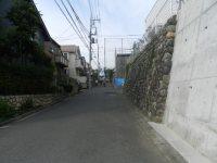 右手に石垣がある家を通り過ぎる=現代法学部2年、田中紘夢さん撮影