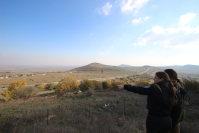 レバノンとの国境付近に建てられた防護壁を指差すイスラエル軍兵士=イスラエル北部ゴラン高原で2015年12月14日、大治朋子撮影
