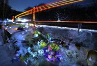 スキーバスが転落した現場に設置された献花台(手前)。長時間露光をかけて撮影すると現場になった国道18号「碓氷バイパス」のカーブに沿って走り抜ける多くの乗用車やトラックの光跡が浮かびあがった=長野県軽井沢町で2016年1月21日午後7時4分、後藤由耶撮影