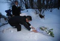 スキーバスが転落した現場に花を手向ける「イーエスピー」の高橋美作社長(手前)=長野県軽井沢町で2016年1月21日午後5時8分、後藤由耶撮影