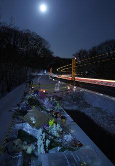 スキーバスが転落した現場には献花台が設けられ、多くの花が手向けられている。その脇の現場のカーブを多くのトラックや乗用車が通り過ぎていた=長野県軽井沢町で2016年1月21日午後5時58分、後藤由耶撮影(30秒露光)
