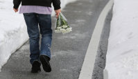 花を手向けるためにバスが転落した現場に向かう女性=長野県軽井沢町で2016年1月21日午後1時36分、後藤由耶撮影