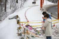 スキーバスが転落した現場に花を手向けて、手を合わせる人たち=長野県軽井沢町で2016年1月21日午後1時56分、後藤由耶撮影