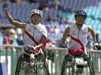 【2000シドニーパラリンピック】女子車いすマラソンで2位の畑中和(左)と3位の土田和歌子。観客の声援に応えて場内を一周した=石井諭撮影