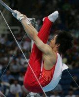【2004アテネ五輪】体操男子団体で金メダル。鉄棒の最終演技者の冨田洋之は離れ技のコールマン、降り技の伸身新月面(伸身2回宙2回ひねり)の着地をしっかりと決めた=尾籠章裕撮影
