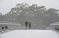 強く降る雪の中を歩く人たち。奥は小倉城=北九州市小倉北区で2016年1月24日午前9時50分、矢頭智剛撮影