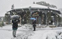 雪に覆われた旧グラバー住宅の前で写真を撮る観光客長崎市南山手町で2016年1月24日午前9時59分、今手麻衣撮影