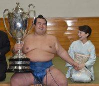 賜杯を手に笑顔の優勝した琴奨菊。右は妻・祐未さん=東京・両国国技館で2016年1月24日午後6時11分、竹内幹撮影