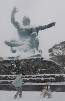 Children play in the snow in front of the peace statue in Nagasaki, on Jan. 24, 2016. (Mainichi)