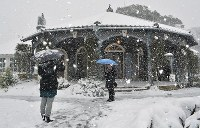 Tourists take a picture in front of the snow-covered Glover Residence, former home of Scottish merchant Thomas Blake Glover, in Nagasaki, on Jan. 24, 2016. (Mainichi)